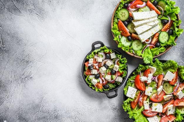 Set van kant-en-klare griekse salade in een kom. witte achtergrond. bovenaanzicht. ruimte kopiëren.