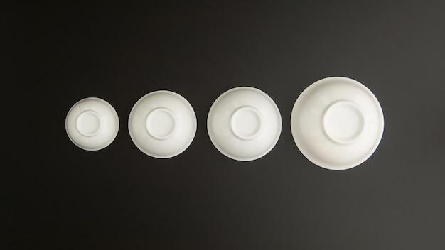 Set van keramische keukenkoppen omgekeerd op zwarte achtergrond, bovenaanzicht