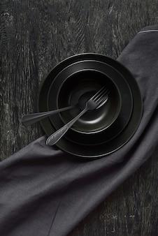 Set van keramische platen zwarte kleuren geserveerd met lepel en vork en textiel handdoek of servet op dezelfde kleur stenen achtergrond, kopieer ruimte. bovenaanzicht.