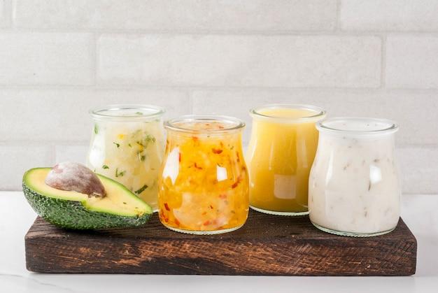 Set van klassieke saladedressings honingmosterd, ranch, vinaigrette, citroen en olijfolie, op een witte marmeren tafel,