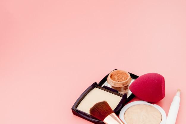 Set van kleurrijke cosmetica op roze houten tafel achtergrond, basis voor make-up in de vorm van een kussen. kopieer ruimte