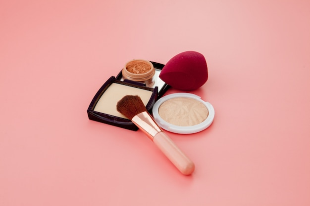 Set van kleurrijke cosmetica op roze houten tafel achtergrond, basis voor make-up in de vorm van een kussen.