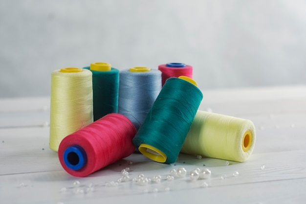 Set van kleurrijke gekleurde ballen van draad op een lichtgekleurde houten ondergrond.