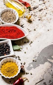 Set van kleurrijke kruiden en specerijen op rustieke tafel.