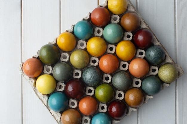 Set van kleurrijke paaseieren gekleurd met natuurlijke kleurstof - kurkuma, ui huid, carcade, rode kool en koffie in karton