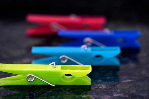Set van kleurrijke wasknijpers, uitgelijnd op zwart graniet