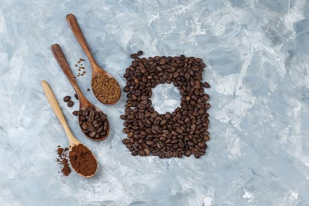 Set van koffiebonen, oploskoffie, koffiemeel in houten lepels en koffiebonen op een lichtblauwe marmeren achtergrond. detailopname.
