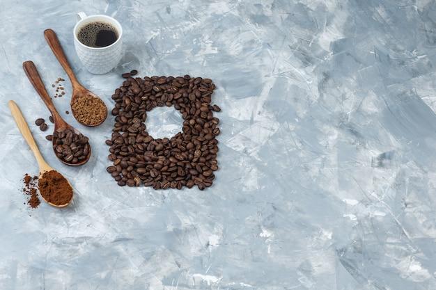 Set van koffiebonen, oploskoffie, koffiemeel in houten lepels en kopje koffie op een lichtblauwe marmeren achtergrond. hoge kijkhoek.