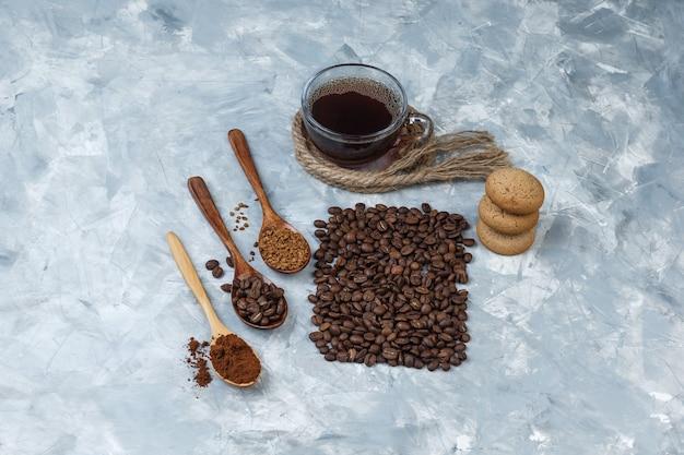 Set van koffiebonen, oploskoffie, koffiemeel in houten lepels, touwen, koekjes en koffiebonen, kopje koffie op een lichtblauwe marmeren achtergrond. plat leggen.