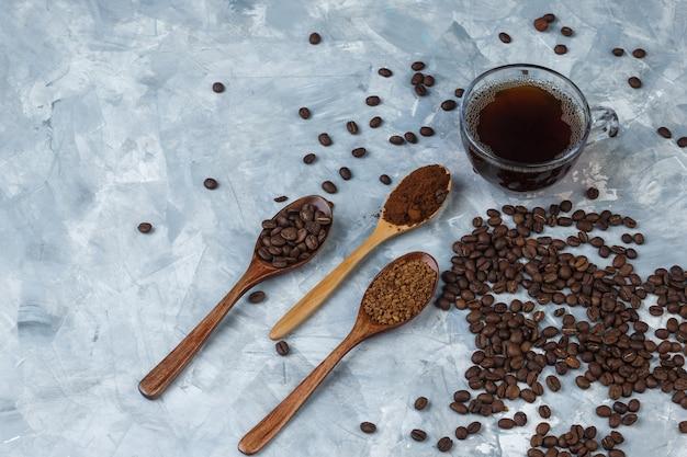 Set van koffiemeel, instant koffie en koffiebonen in houten lepels en koffiebonen, kopje koffie op een lichtblauwe marmeren achtergrond. detailopname.