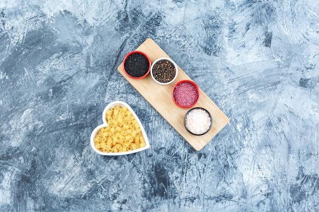 Set van kruiden en ditalini pasta in een kom op grijze gips en houten stuk achtergrond. bovenaanzicht.