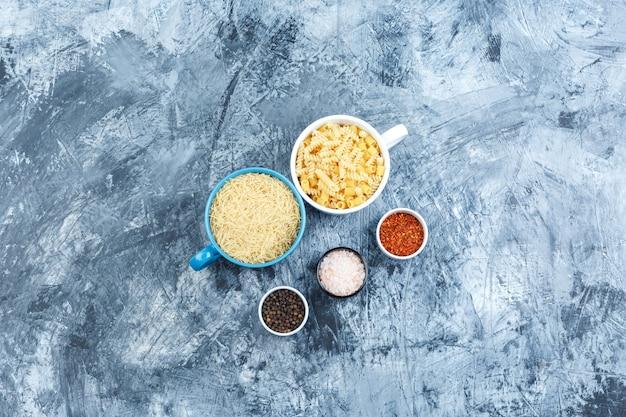 Set van kruiden en diverse pasta in kommen op een grijze gips achtergrond. bovenaanzicht.
