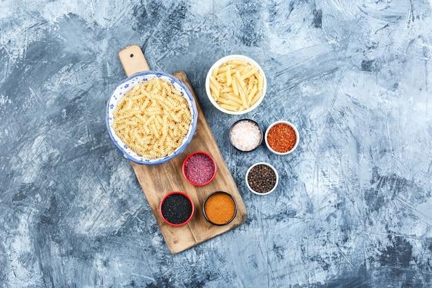 Set van kruiden en diverse pasta in kommen op grijze gips en snijplank achtergrond. bovenaanzicht.