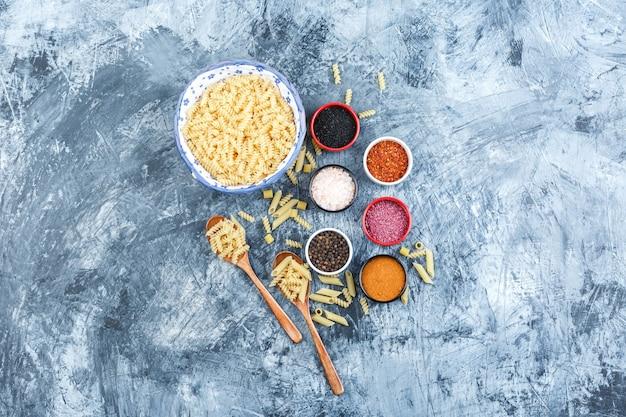 Set van kruiden en fusilli pasta in kom en houten lepels op een grijze gips achtergrond. bovenaanzicht.