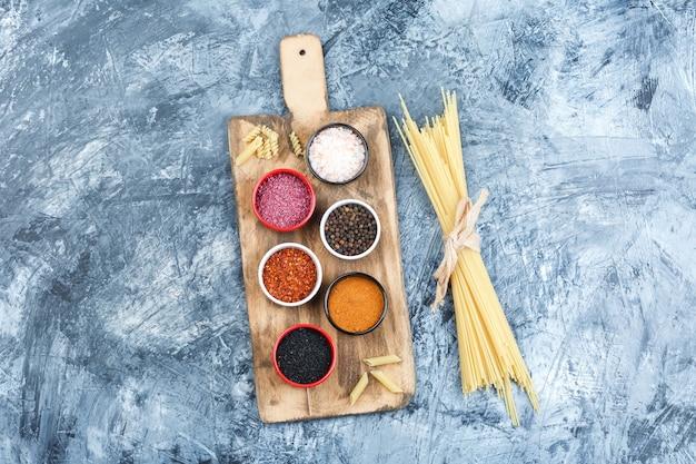 Set van kruiden en spaghetti op grijze gips en snijplank achtergrond. bovenaanzicht.