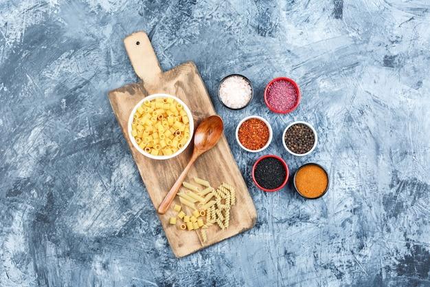Set van kruiden, houten lepel en ditalini pasta in een kom op grijze gips en snijplank achtergrond. bovenaanzicht.