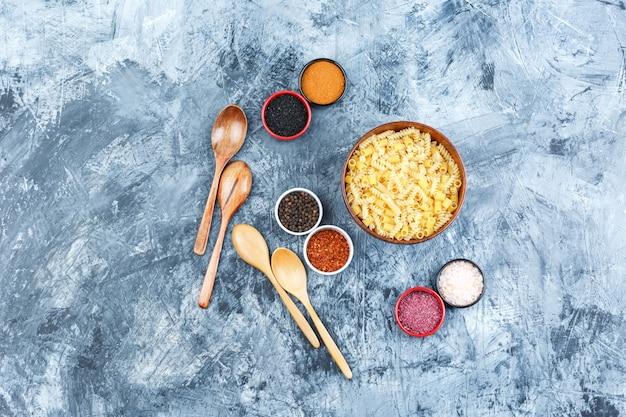 Set van kruiden, houten lepels en rauwe pasta in een kom op een grijze gips achtergrond. bovenaanzicht.