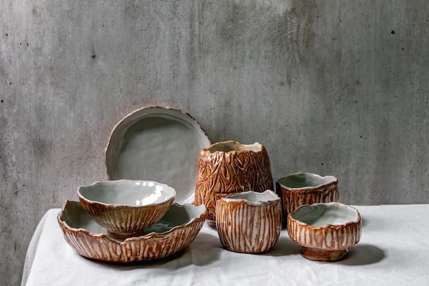 Set van lege ambachtelijke keramische kommen dekken door grijze en bruine textuurglazuur op wit linnen tafelkleed met grijze muur erachter