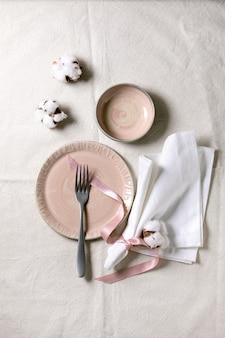 Set van lege roze keramische borden met vork en textielservet,