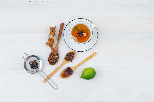 Set van limoen, kruiden en specerijen en kruidenthee op een wit oppervlak