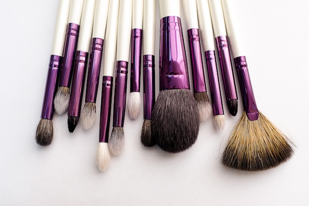 Set van make-up artiest borstels voor professionele make-up in een schoonheidssalon, op een witte achtergrond. het concept van cosmetica, lichaams- en gezichtsverzorging.