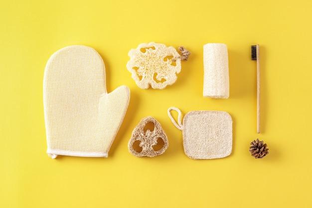 Set van milieuvriendelijke badkameraccessoires, gereedschap voor in bad, natuurlijke bamboe tandenborstel, spons. zero waste cosmeticaproducten op geel.