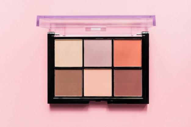 Set van naakt oogschaduw in zwart geval op roze achtergrond. bovenaanzicht, kopie ruimte