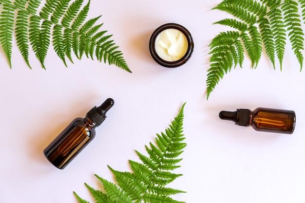Set van natuurlijke biologische gezichtscrème en etherische olie op varenbladeren. kopieer ruimte voor uw cosmeticamerkontwerp.
