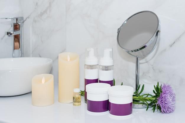 Set van natuurlijke cosmetica in schoonheidssalon potten en flessen van lichaams- of haarverzorgingsproduct op tafel met bloemen.