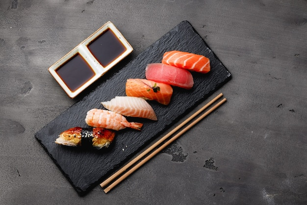 Set van nigiri sushi geserveerd op plaat op grijze tafel