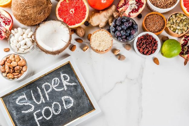 Set van organische gezonde voeding voedsel superfoods bonen peulvruchten noten zaden groenen fruit en groenten witte achtergrond