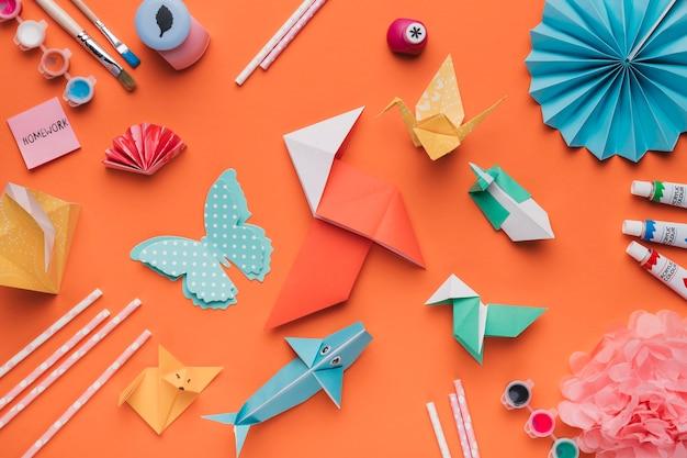 Set van origami papier kunst; penseel; waterverf en stro op oranje achtergrond