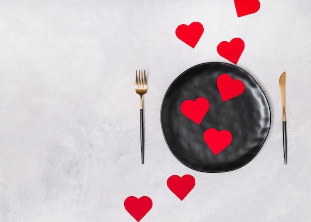 Set van ornament harten op zwarte plaat tussen bestek