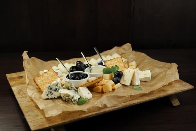 Set van: parmezaanse kaas, goudse kaas, feta, blauwe kaas met zoete honing en rode bosbessenjam, versierd met geurige basilicumblaadjes en olijven op een houten bord in een restaurant op tafel.