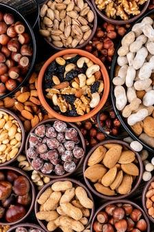 Set van pecannoten, pistachenoten, amandel, pinda, cashewnoten, pijnboompitten en diverse noten en gedroogde vruchten in een mini verschillende kommen en zwarte pan. bovenaanzicht.