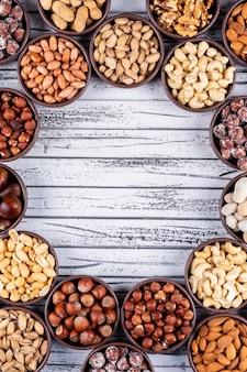 Set van pecannoten, pistachenoten, amandel, pinda en diverse noten en gedroogde vruchten in een cyclusvormige mini verschillende kommen