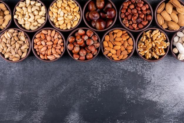 Set van pecannoten, pistachenoten, amandel, pinda's en een rij van diverse noten en gedroogde vruchten in verschillende mini-kommen