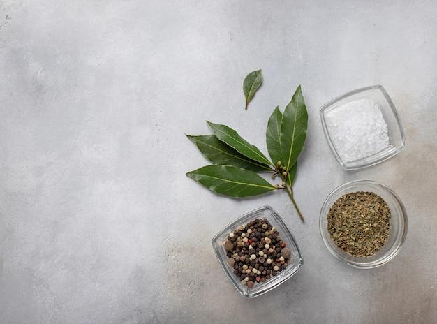 Set van peper, kruiden, zout en laurier ingrediënten voor het koken van grijs oppervlak, bovenaanzicht,