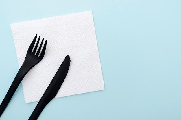 Set van plastic bestek zwarte vork en mes op witboek servet