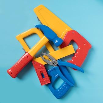 Set van plastic speelgoed tools in een hoop op een blauwe achtergrond