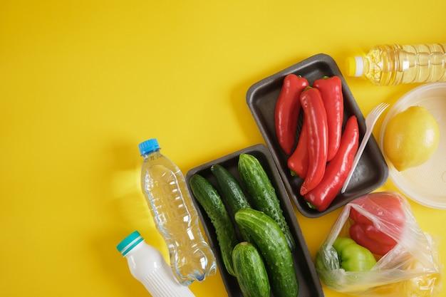 Set van producten in verschillende plastic verpakkingen, plastic milieuvervuiling concept, zeg nee tegen plastic, gele achtergrond kopie ruimte bovenaanzicht