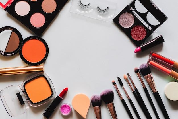 Set van professionele cosmetica: make-up kwasten, schaduwen, lippenstift - geïsoleerd op lichte achtergrond. bovenaanzicht. plaats voor uw tekst.