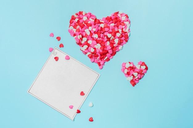 Set van rode harten van kleine decoraties in de buurt van papier