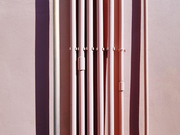 Set van roze verticale waterleidingen tegen roze muur