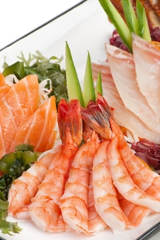 Set van sashimi op daikon (witte radijs). gegarneerd met gember, zeewier, komkommer