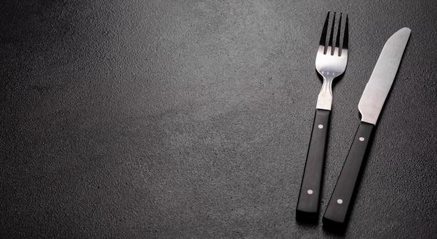 Set van servies klaar voor de maaltijd met zwarte kopie ruimte. metalen mes, vork, lepel en plaat