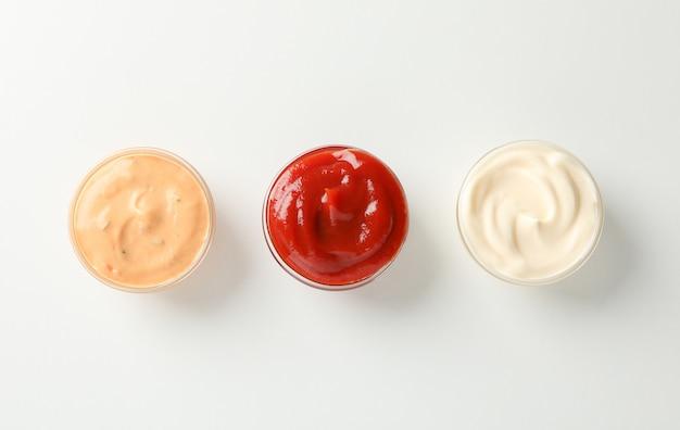 Set van smakelijke sauzen op witte achtergrond, ruimte voor tekst. bovenaanzicht