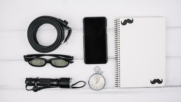Set van smartphone in de buurt van notebook en mannelijke accessoires