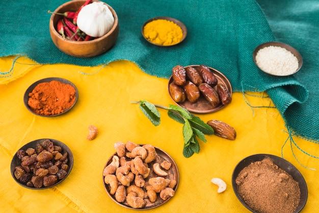 Set van specerijen in de buurt van gedroogde vruchten en noten
