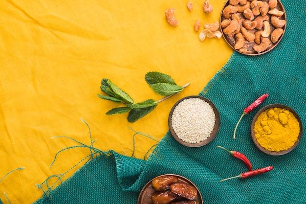 Set van specerijen in de buurt van planten, gedroogde vruchten en noten